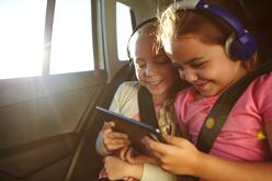two girls using tablet in the car