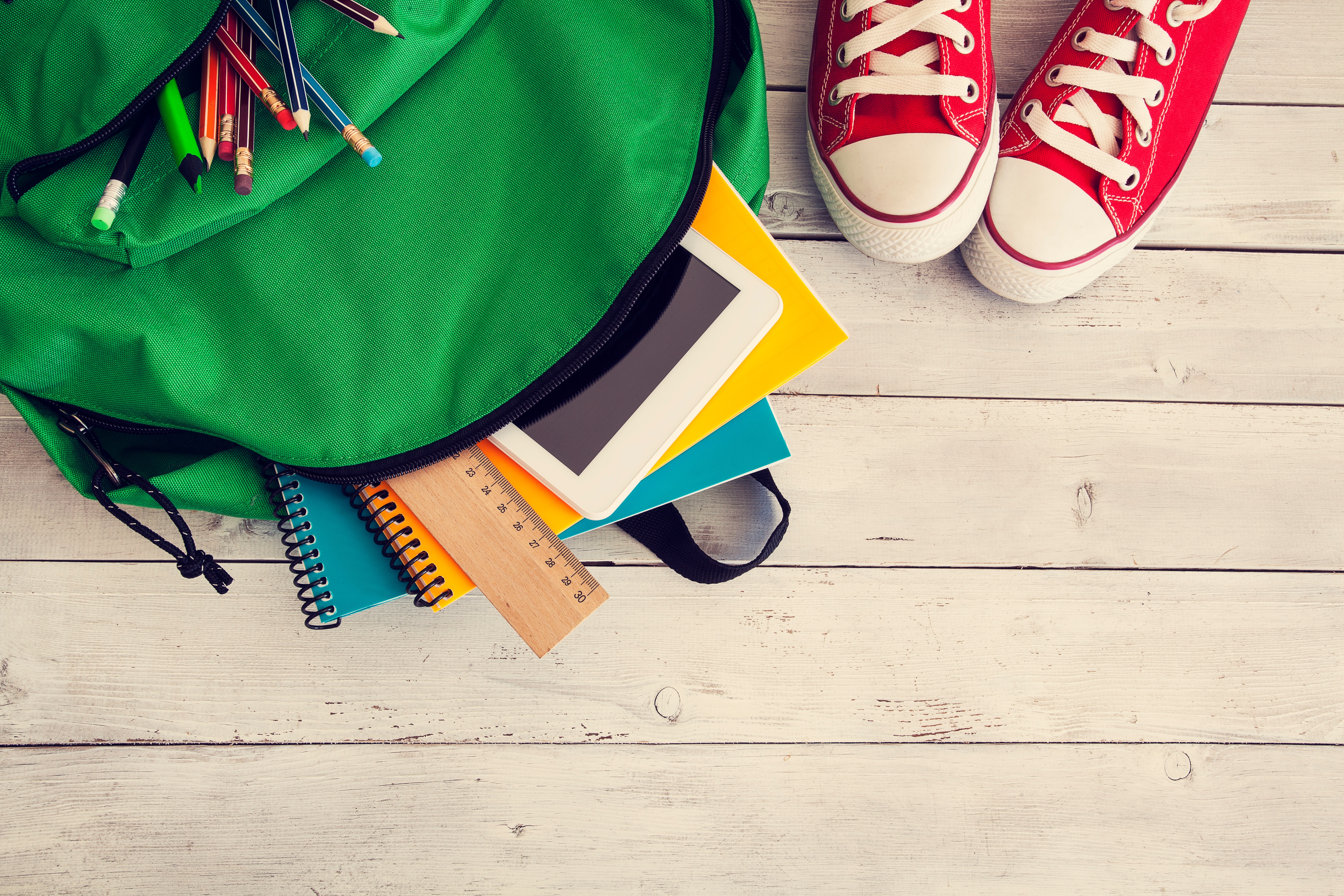 Back to School Background_backpack, converse shoes, wood_iStock-607605540