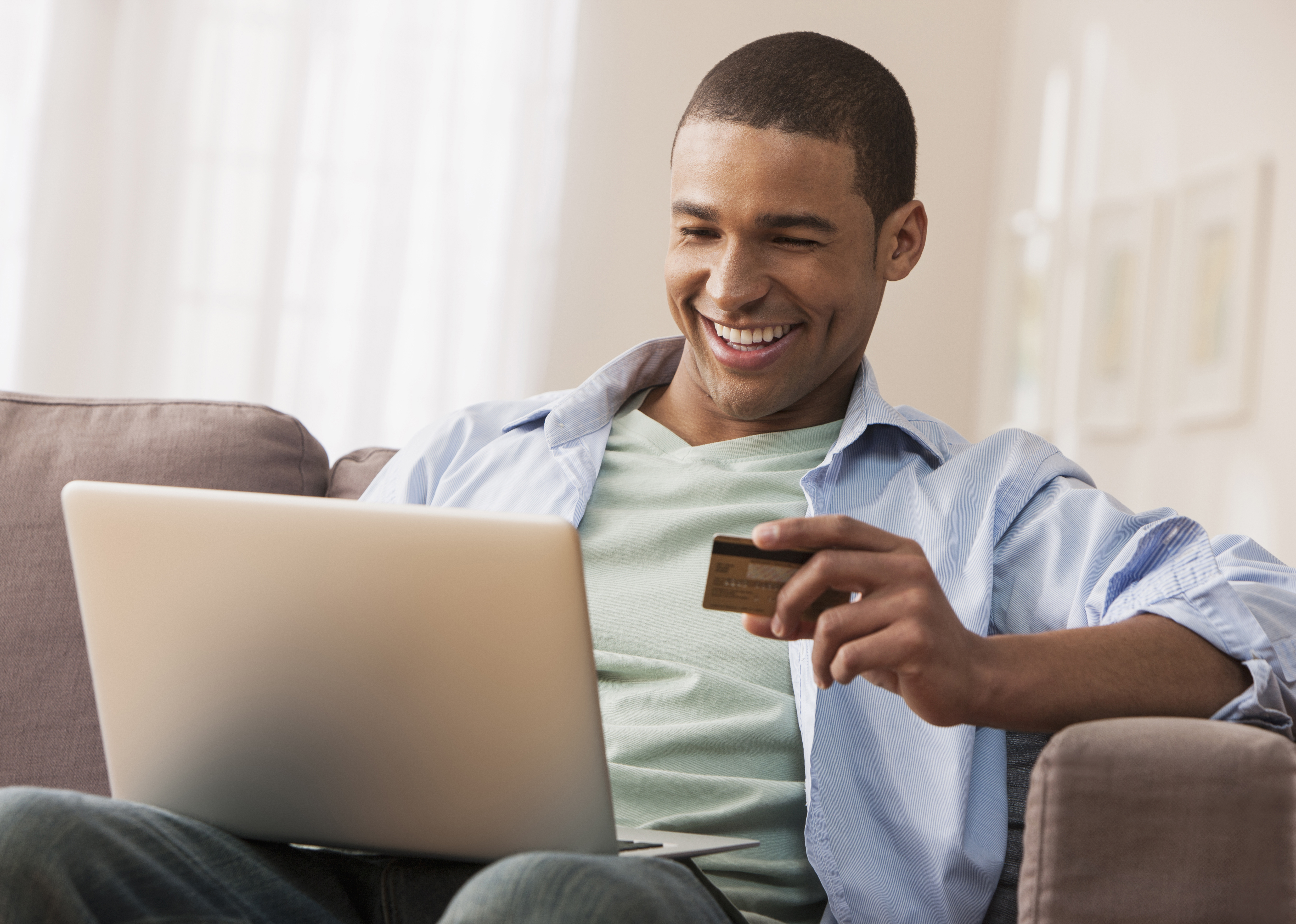 iStock-155773494-man laptop credit card on couch